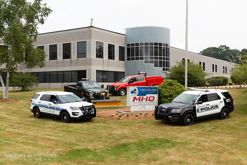 Law enforcement vehicles, red truck and gray truck parked outside of MHQ headquarters