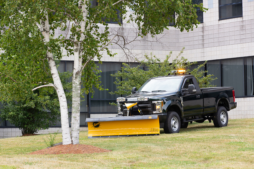 Black pick-up truck with yellow snow plow attached to front and yellow lights